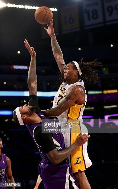 Jordan Hill of the Los Angeles Lakers shoots over DeMarcus Cousins of the Sacramento Kings at Staples Center on November 24, 2013 in Los Angeles,...