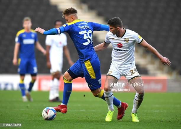 Jordan Houghton of Milton Keynes Dons challenges Joe Pigott of AFC Wimbledon during the Sky Bet League One match between Milton Keynes Dons and AFC...