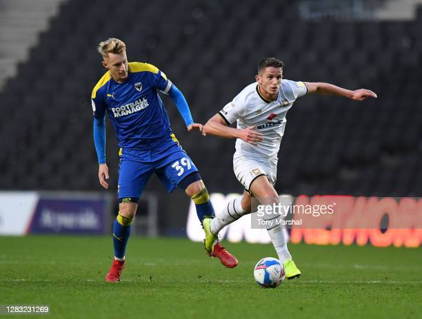 Jordan Houghton of Milton Keynes Dons is challenged by Joe Pigott of AFC Wimbledon during the Sky Bet League One match between Milton Keynes Dons and...