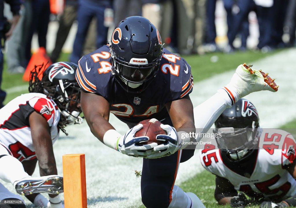 Jordan Howard #24 of the Chicago Bears dives into the end zone for a touchdown past Desmond Trufant #21 (L) and Deion Jones #45 of the Atlanta Falcons during the season opening game at Soldier Field on September 10, 2017 in Chicago, Illinois.