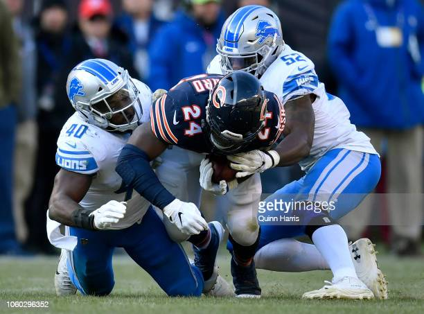 Jordan Howard of the Chicago Bears is tackled by Jarrad Davis and Christian Jones of the Detroit Lions in the third quarter at Soldier Field on...