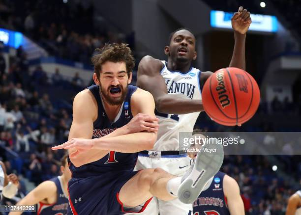 Jordan Hunter of the Saint Mary's Gaels and Dhamir CosbyRoundtree of the Villanova Wildcats compete for a rebound in the first half during the first...