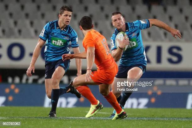 Jordan Hyland of the Blues is supported by Matt Duffie is tackled during the Super Rugby round 11 match between the Blues and Jaguares at Eden Park...