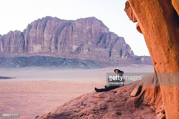 Jordan, Japanese woman sitting on top of a rock in Wadi Rum