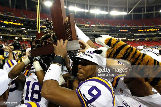Jordan Jefferson of the LSU Tigers helps carry the 2011 SEC Championship trophy after their 4210 win over the Georgia Bulldogs at Georgia Dome on...