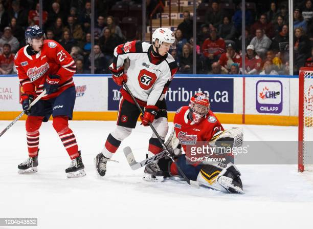 Jordan Kooy of the Oshawa Generals makes a glove save in the second period while his teammate David Jesus and Alec Belanger of the Ottawa 67's look...
