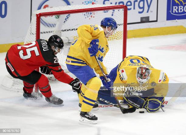 Jordan Kyrou of Canada jams at a rebound in front of Filip Gustavsson and Lias Andersson of Sweden during the first period of play in the IIHF World...