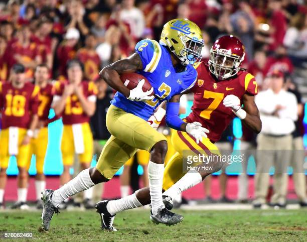 Jordan Lasley of the UCLA Bruins runs after his catch as he is chased by Marvell Tell III of the USC Trojans during the second quarter at Los Angeles...