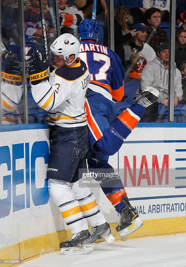 Jordan Leopold #3 of the Buffalo Sabres is checked into the boards by Matt Martin #17 of the New York Islanders at Nassau Veterans Memorial Coliseum on February 9, 2013 in Uniondale, New York.
