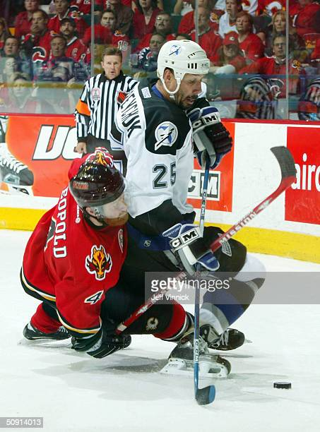 Jordan Leopold of the Calgary Flames and Dave Andreychuk of the Tampa Bay Lightning get tangledup while fighting for the puck during the second...
