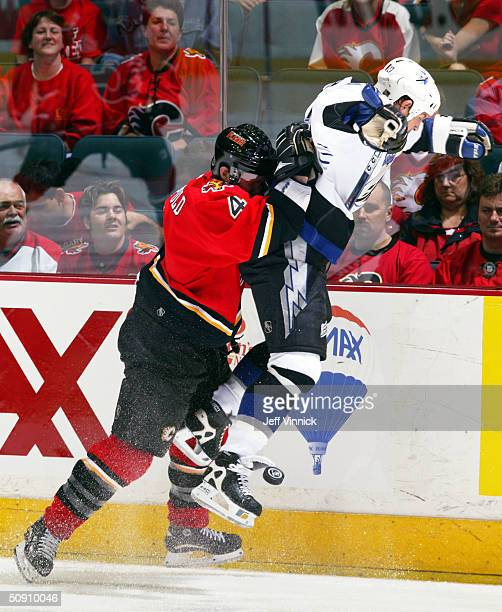 Jordan Leopold of the Calgary Flames hits Tim Taylor of the Tampa Bay Lightning from behind during the third period in game three of the NHL Stanley...