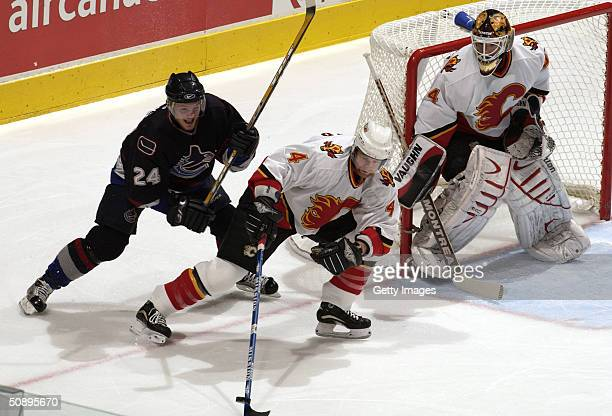 Jordan Leopold of the Calgary Flames looks to control the puck against Matt Cooke of the Vancouver Canucks while goaltender Miikka Kiprusoff of the...