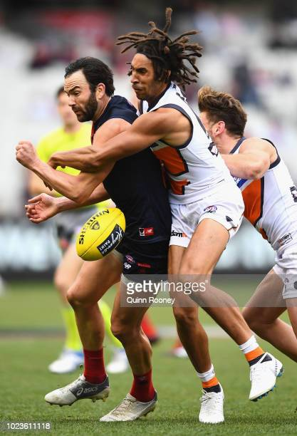 Jordan Lewis of the Demons handballs whilst being tackled by Aiden Bonar of the Giants during the round 23 AFL match between the Melbourne Demons and...