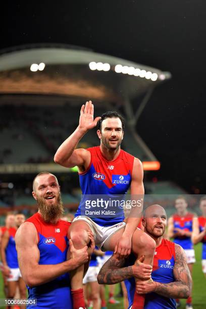 Jordan Lewis of the Demons is chaired from the field by Max Gawn of the Demons and Nathan Jones of the Demons after his 300th AFL game during the...