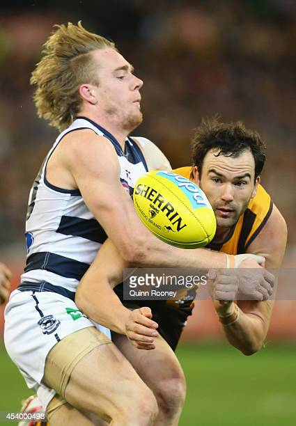 Jordan Lewis of the Hawks handballs whilst being tackled by Cameron Guthrie of the Cats during the round 22 AFL match between the Hawthorn Hawks and...