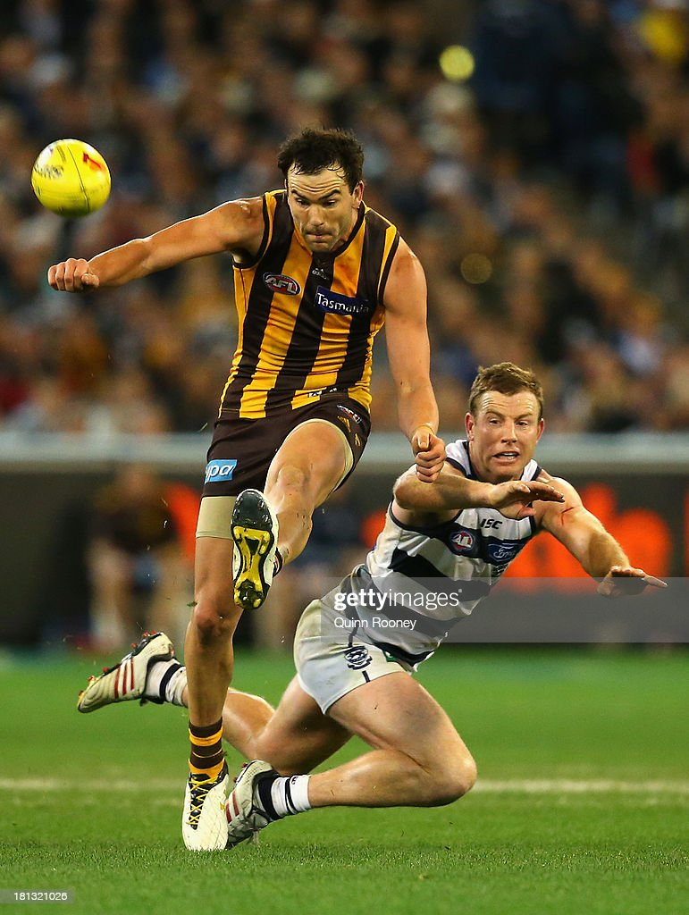Jordan Lewis of the Hawks kicks whilst Steve Johnson of the Cats attempts to smouther during the AFL First Preliminary Final match between the Hawthorn Hawks and the Geelong Cats at the Melbourne Cricket Ground on September 20, 2013 in Melbourne, Australia.