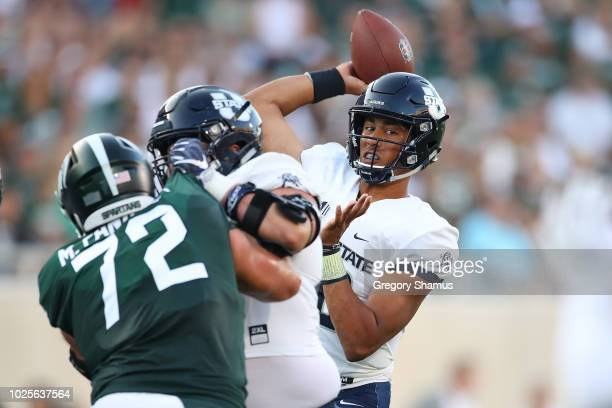Jordan Love of the Utah State Aggies throws a first half pass behind Mike Panasiuk of the Michigan State Spartans at Spartan Stadium on August 31...