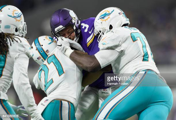 Jordan Lucas and Jesse Davis of the Miami Dolphins tackle Mitch Leidner of the Minnesota Vikings during the third quarter in the preseason game on...