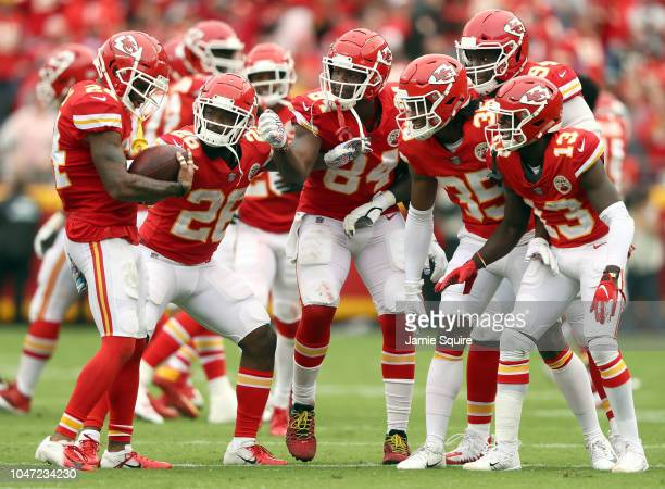 Jordan Lucas of the Kansas City Chiefs holds the football like a baby as teammates look on after intercepting a pass during the game against the...