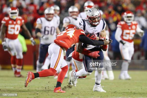 Jordan Lucas of the Kansas City Chiefs tackles Julian Edelman of the New England Patriots in the second half during the AFC Championship Game at...