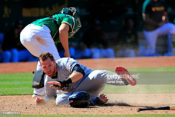 Jordan Luplow of the Cleveland Indians slides into home before the tag by Ramon Laureano of the Oakland Athletics during the ninth inning at...
