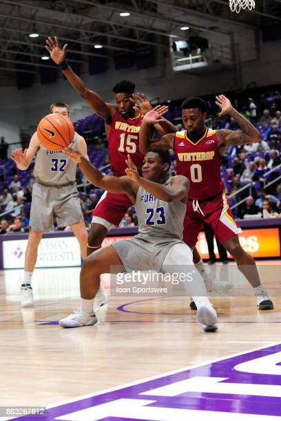 Jordan Lyons guard Furman University Paladins passes the basketball while falling to the Ingles Floor against Nych Smith guard and Jermaine Ukaegbu...