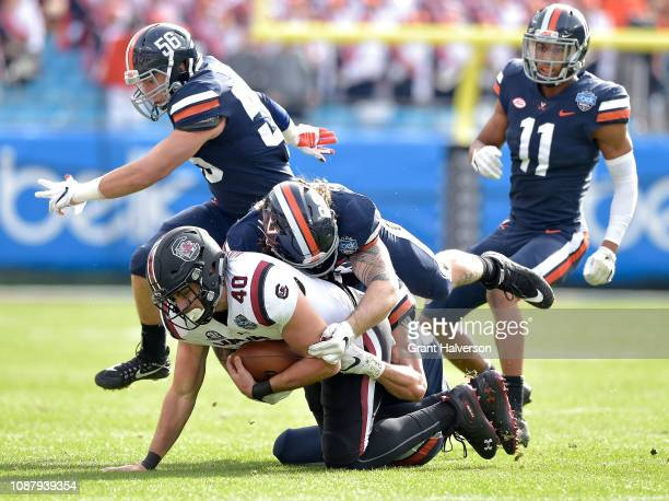 Jordan Mack of the Virginia Cavaliers tackles Jacob August of the South Carolina Gamecocks during the first half of the Belk Bowl at Bank of America...