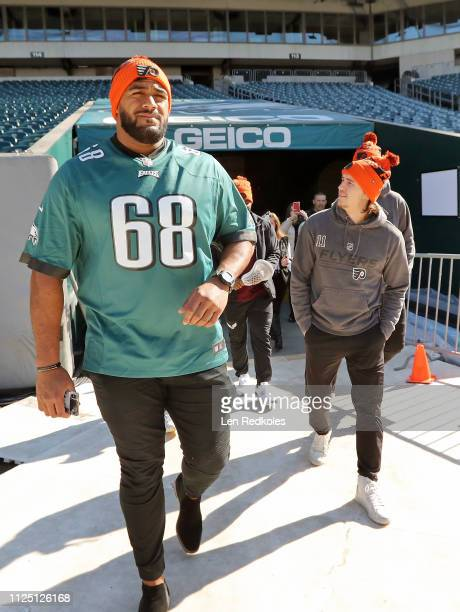 Jordan Mailata of the Philadelphia Eagles walks onto the field with Travis Konecny of the Phialdelphia Flyers as they look at the preparations for...