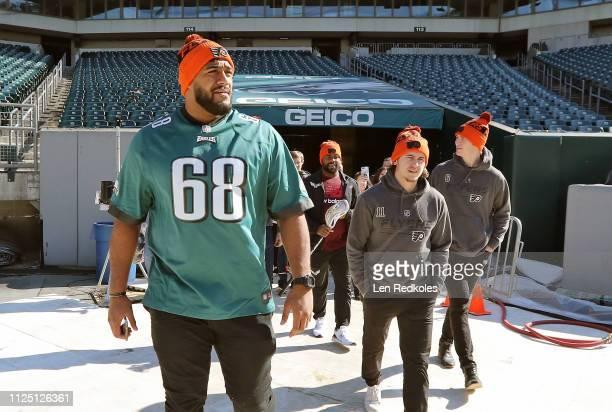 Jordan Mailata of the Philadelphia Eagles walks onto the field with Travis Konecny and Travis Sanheim of the Philadelphia Flyers and Trevor Baptise...