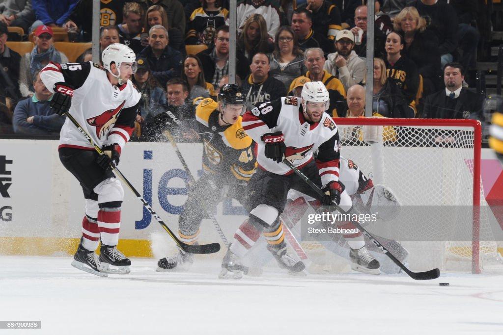 Jordan Martinook #48 and Kyle Capobianco #75 of the Arizona Coyotes against Danton Heinen #43 of the Boston Bruins at the TD Garden on December 7, 2017 in Boston, Massachusetts.