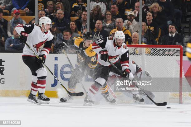 Jordan Martinook and Kyle Capobianco of the Arizona Coyotes against Danton Heinen of the Boston Bruins at the TD Garden on December 7 2017 in Boston...