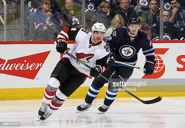 Jordan Martinook of the Arizona Coyotes and Jacob Trouba of the Winnipeg Jets follow the play up the ice during third period action at the MTS Centre...