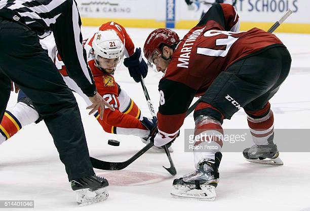 Jordan Martinook of the Arizona Coyotes and Vincent Trocheck of the Florida Panthers battle for a faceoff during the second period at Gila River...