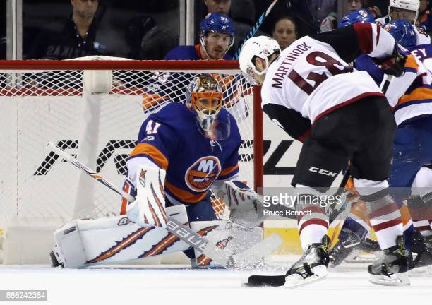 Jordan Martinook of the Arizona Coyotes attempts to get a shot off against Jaroslav Halak of the New York Islanders the Barclays Center on October 24...