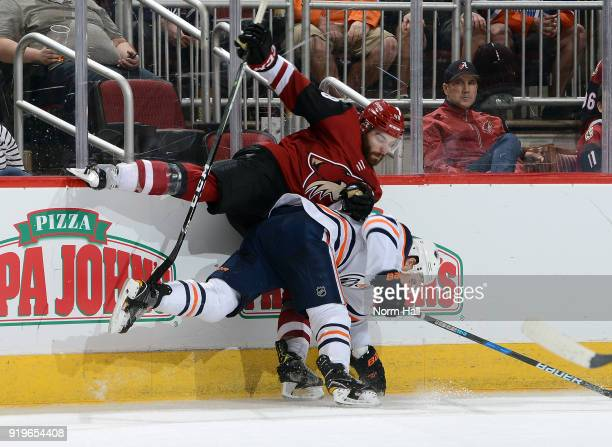 Jordan Martinook of the Arizona Coyotes checks Kris Russell of the Edmonton Oilers along the boards during the second period at Gila River Arena on...
