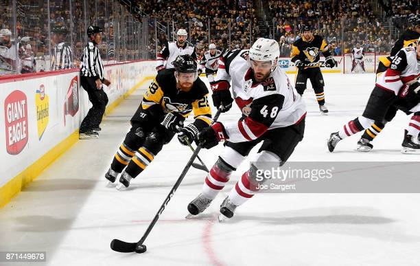 Jordan Martinook of the Arizona Coyotes handles the puck against Ian Cole of the Pittsburgh Penguins at PPG Paints Arena on November 7 2017 in...