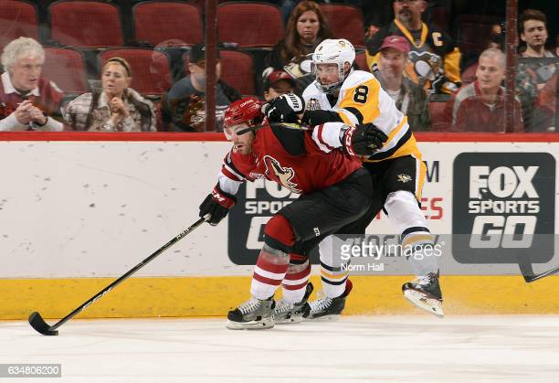 Jordan Martinook of the Arizona Coyotes is grabbed by Brian Dumoulin of the Pittsburgh Penguins as he skates with the puck during the third period at...