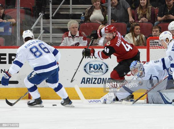 Jordan Martinook of the Arizona Coyotes passes the puck while being defended by Andrei Vasilevskiy and Nikita Kucherov of the Tampa Bay Lightning at...
