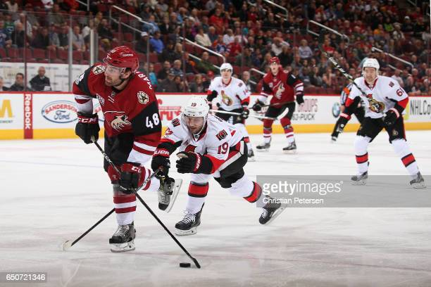 Jordan Martinook of the Arizona Coyotes skates in with the puck ahead of Derick Brassard of the Ottawa Senators during the first period of the NHL...