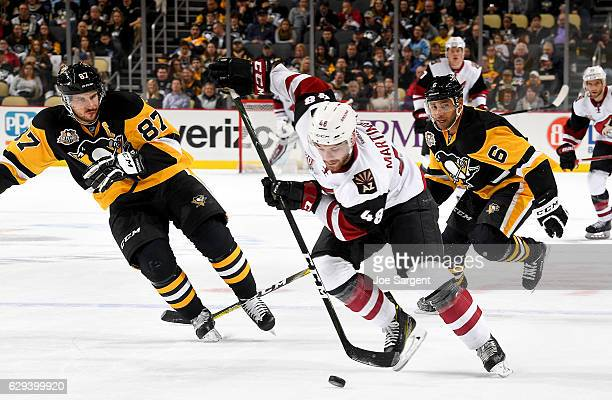 Jordan Martinook of the Arizona Coyotes skates the puck up ice against Sidney Crosby and Trevor Daley of the Pittsburgh Penguins at PPG Paints Arena...