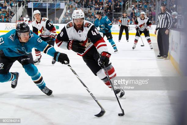 Jordan Martinook of the Arizona Coyotes skates with the puck against Justin Braun of the San Jose Sharks at SAP Center on February 13 2018 in San...