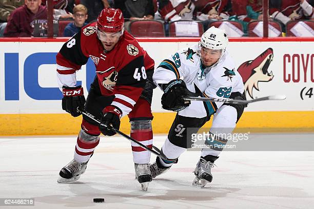 Jordan Martinook of the Arizona Coyotes skates with the puck under pressure from Kevin Labanc of the San Jose Sharks during the first period of the...