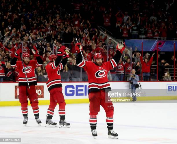 Jordan Martinook of the Carolina Hurricanes celebrates victory during the Storm Surge with teammates Dougie Hamilton and Jaccob Slavin during an NHL...