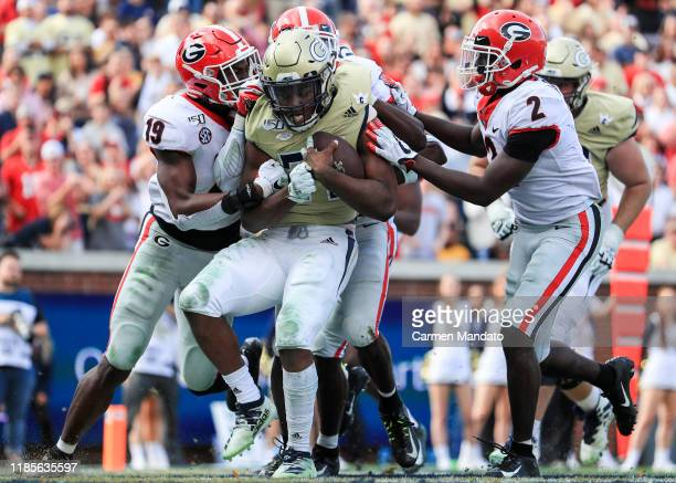 Jordan Mason of the Georgia Tech Yellow Jackets is driven backwards by Richard LeCounte and Adam Anderson of the Georgia Bulldogs during the second...