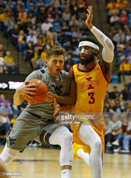 Jordan McCabe of the West Virginia Mountaineers drives the lane against Tre Jackson of the Iowa State Cyclones at the WVU Coliseum on February 5 2020...