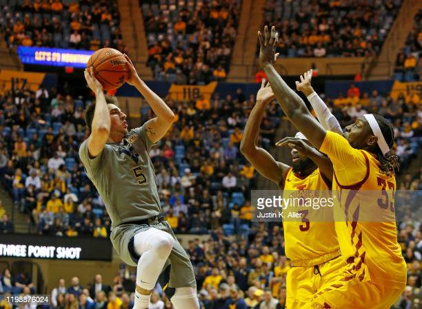 Jordan McCabe of the West Virginia Mountaineers pulls up for a shot against Tre Jackson and Solomon Young of the Iowa State Cyclones at the WVU...