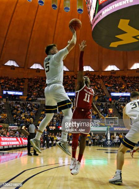 Jordan McCabe of the West Virginia Mountaineers pulls up for a shot against De'Vion Harmon of the Oklahoma Sooners at the WVU Coliseum on February 29...