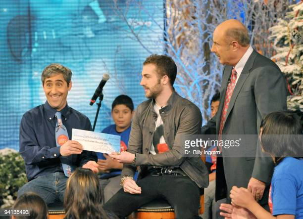 Jordan McGraw presents a check for $50000000 to David Wish founder of Little Kids Rock on behalf of the Dr Phil McGraw Foundation's and Dr Phil...