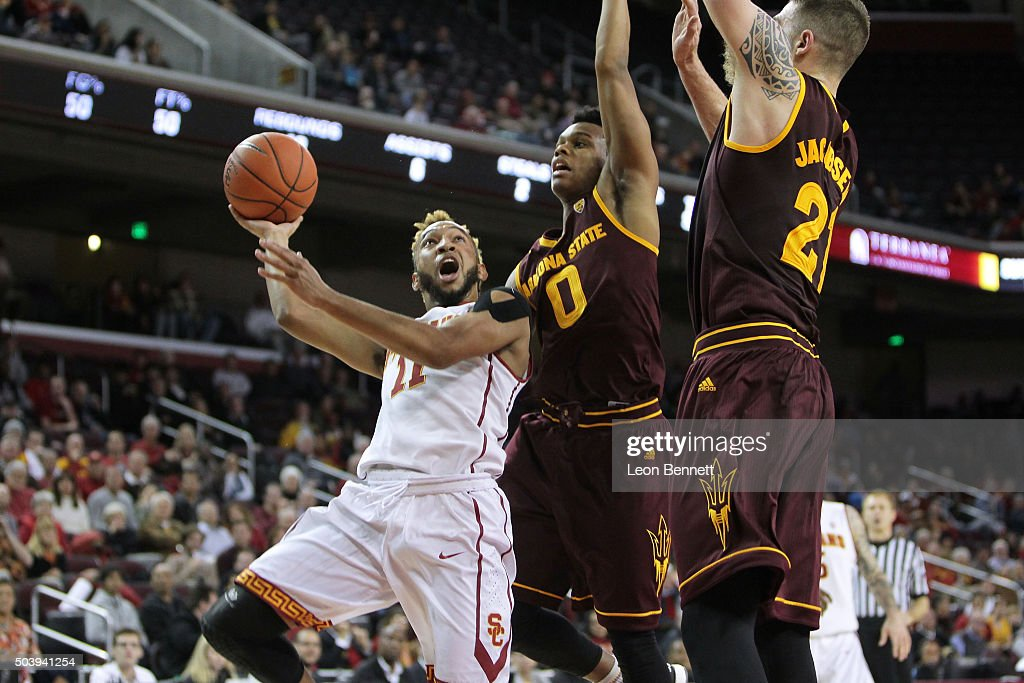 Jordan McLaughlin #11 of the USC Trojans drives to the basket against Tra Holder #0 and Eric Jacobsen #21 of the Arizona State Sundevils during a NCAA Pac12 college basketball game at Galen Center on January 7, 2016 in Los Angeles, California.