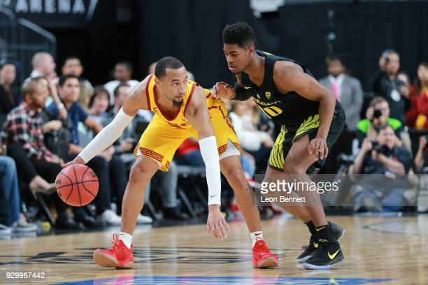 Jordan McLaughlin of the USC Trojans handles the ball against Victor Bailey Jr #10 of the Oregon Ducks during a semifinal game of the Pac12...